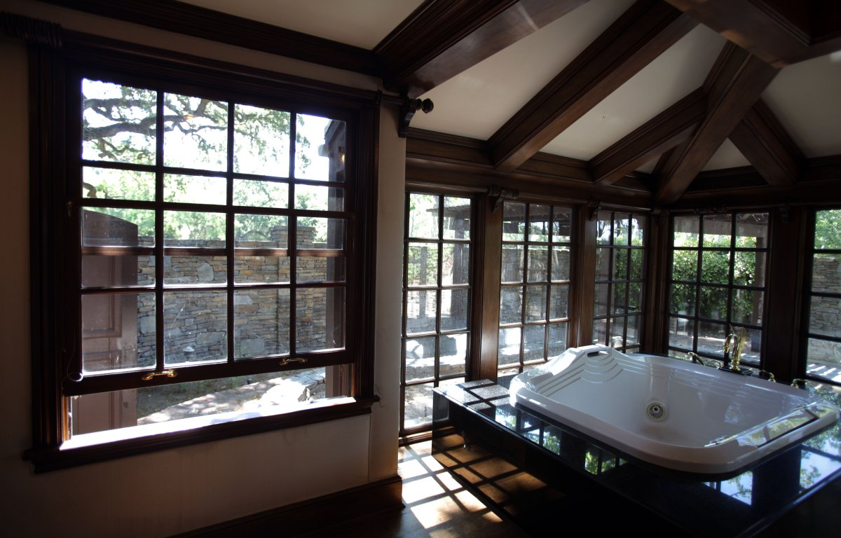a-large-jacuzzi-bath-is-situated-against-the-windows-in-the-master-bathroom
