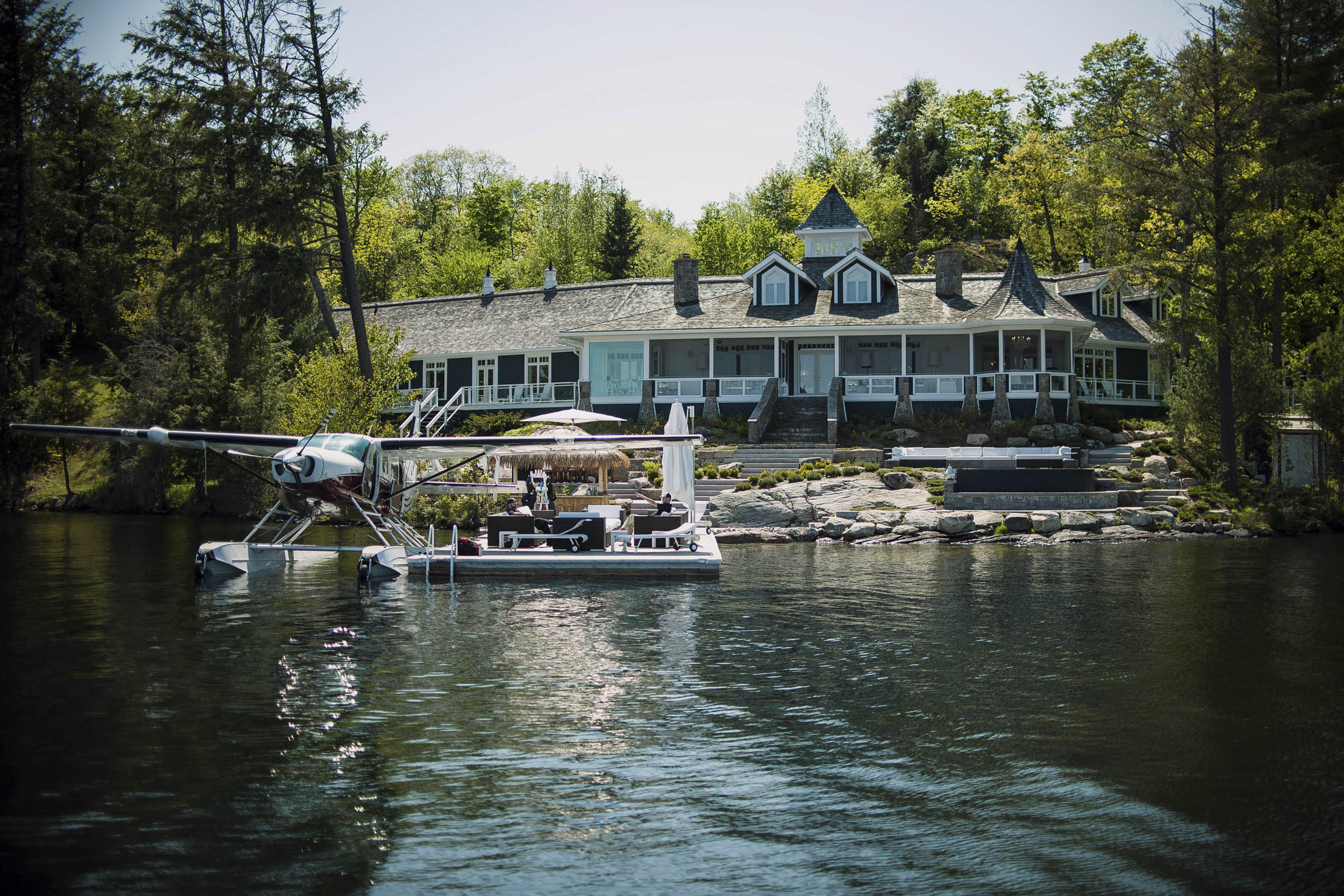 A float plane sits docked outside of a cottage on Lake Jo in Muskoka, Ontario, Canada, on Saturday, May 23, 2015. The Canadian sanctuary of Muskoka, once given away for free by the government and now a treasured spot for the titans of business, is attracting American investors who want a rustic retreat that comes with 800-thread-count sheets. Photographer: James MacDonald/Bloomberg