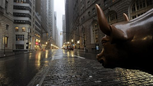 The Wall Street bronze Bull looks out to an empty Broadway