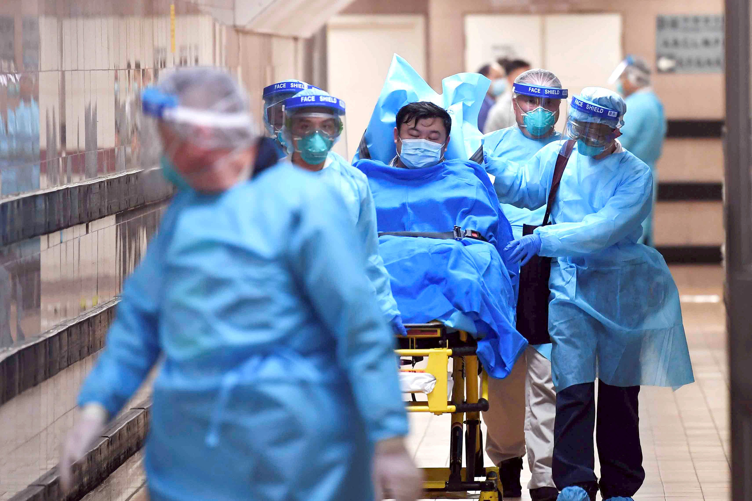 Image: Medical staff transfer a patient of a highly suspected case of a new coronavirus at the Queen Elizabeth Hospital in Hong Kong